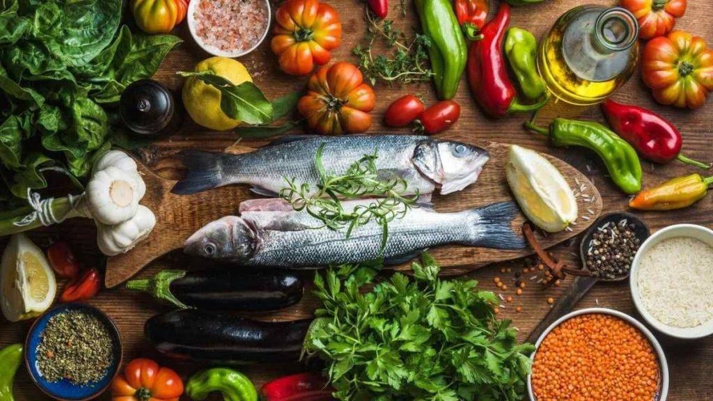 tavola con pesce ortaggi e verdure