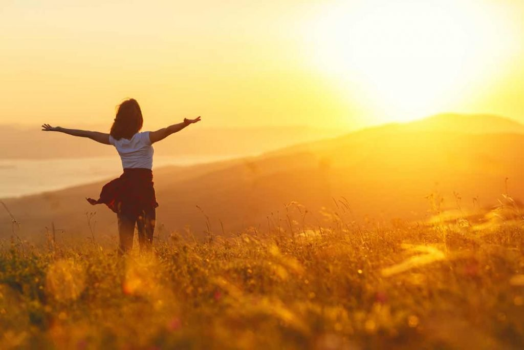 donna con braccia aperte verso il sole
