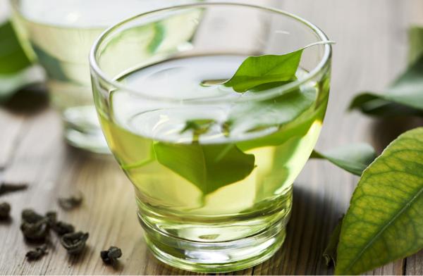 bicchiere con tè verde e foglie